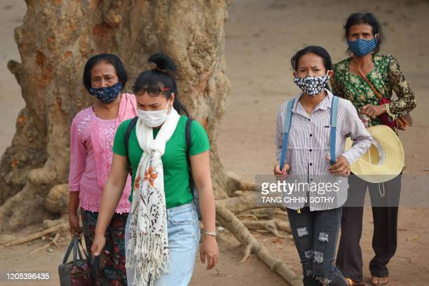 People wear facemask, amid concerns over the spread of the COVID-19 novel coronavirus, as they visit the Angkor Wat temple in Siem Reap province on...