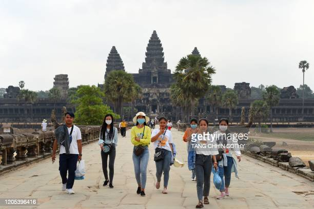 People wear facemasks, amid concerns about the spread of the COVID-19 novel coronavirus, as they visit the Angkor Wat temple in Siem Reap province on...