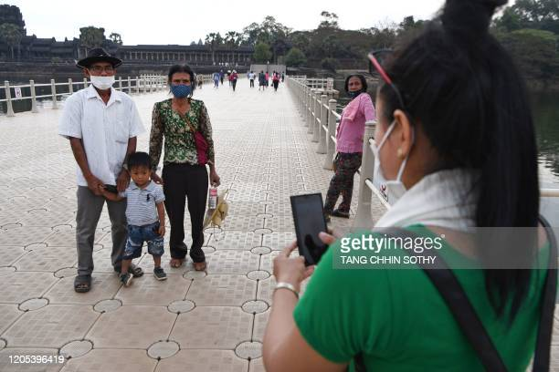 People wear facemasks, amid concerns about the spread of the COVID-19 novel coronavirus, as they pose for a photograh during their visit to the...