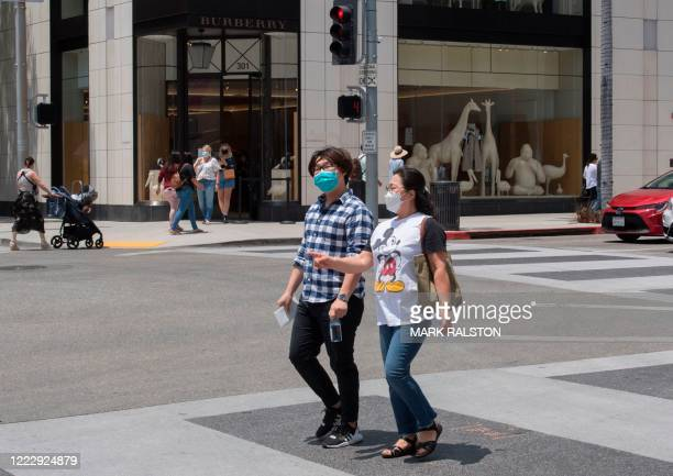 People wear facemasks as shoppers return to the streets of iconic Rodeo Drive as the luxury goods stores reopen after three months of closure due to...