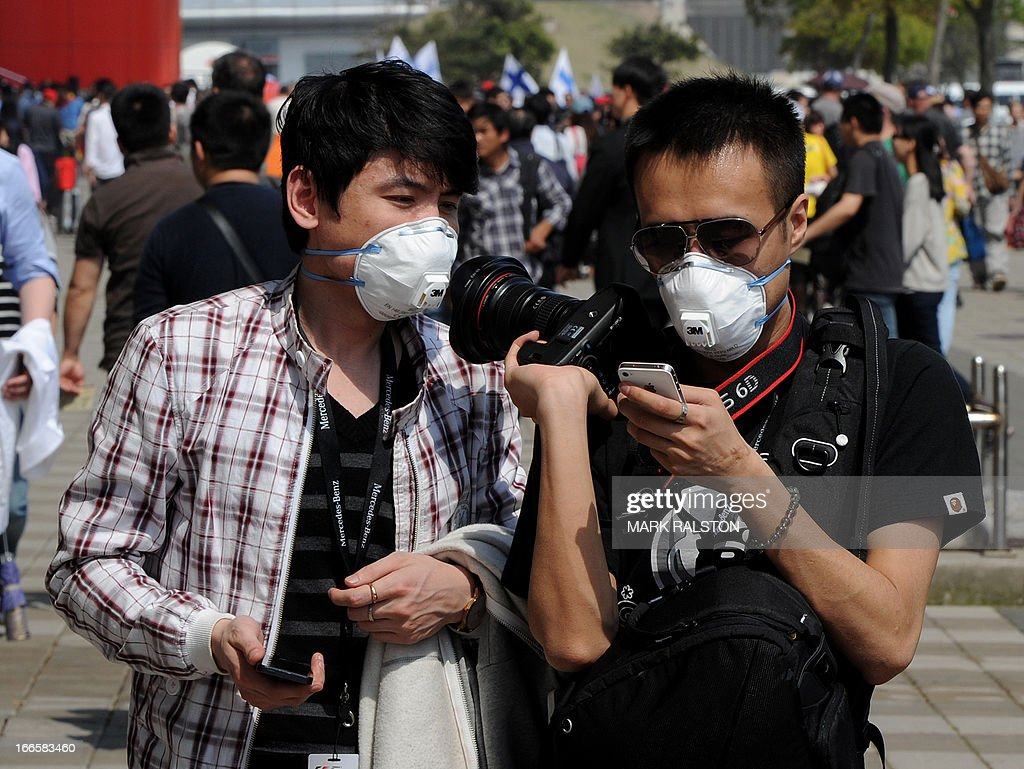 People wear facemasks due to the recent outbreak of bird flu as fans arrive before the start of the Formula One Chinese Grand Prix in Shanghai on April 14, 2013. AFP PHOTO / Mark RALSTON