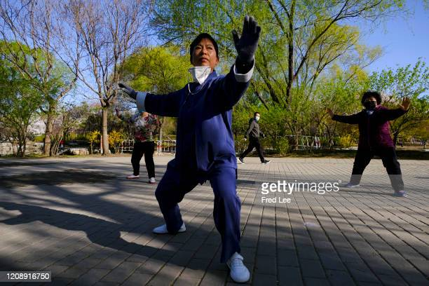 People wear masks as part of precautionary measures against the spread of the COVID19 as they perform Tai Chi on April 02 2020 in Beijing China...