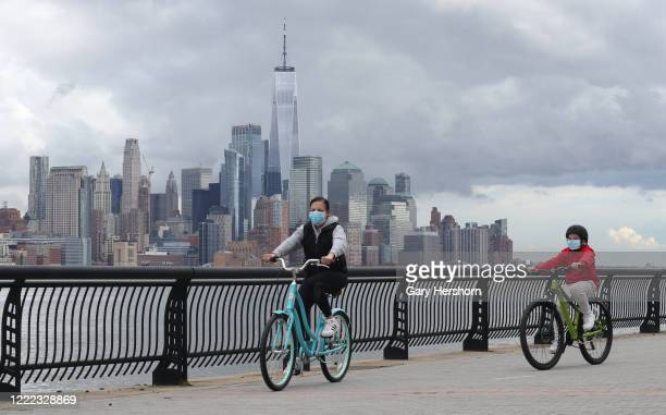 People wear masks as they ride their bicycles in front of the skyline of lower Manhattan and One World Trade Center in New York City on May 1 2020 in...