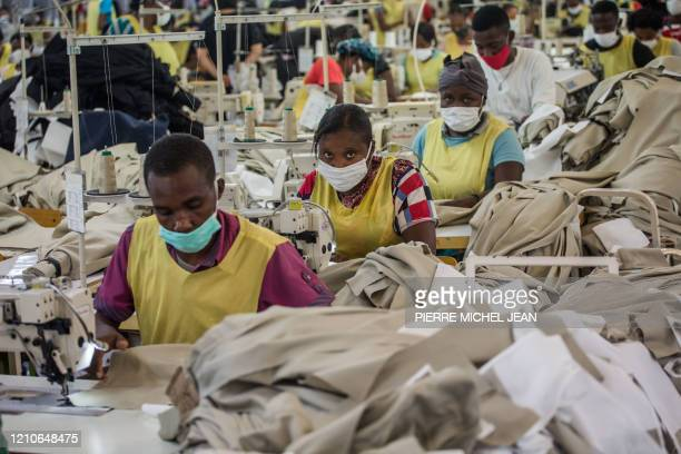People wear masks as they work at the MBI factory at the industrial park Sonapi in Port-au-Prince on April 21, 2020. - A month after the country's...