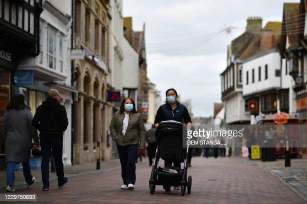People wear masks because of the coronavirus pandemic in the high street in Canterbury, southern England on November 23, 2020. - British Prime...