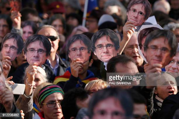 People wear masks depecting ousted separatist leader Carles Puigdemont during a demonstration on January 30 2018 in Barcelona The speaker of...