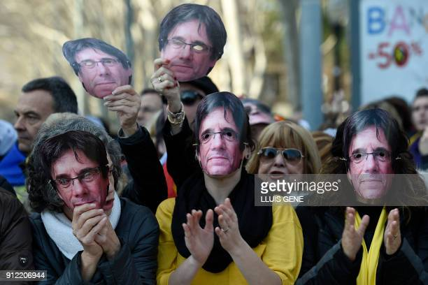 TOPSHOT People wear masks depecting ousted separatist leader Carles Puigdemont during a demonstration on January 30 2018 in Barcelona The speaker of...