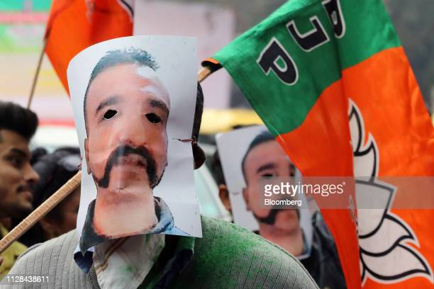 People wear masks in the likeness of Indian Air Force pilot Abhinandan Varthaman and hold Bharatiya Janata Party flags during a rally in New Delhi...