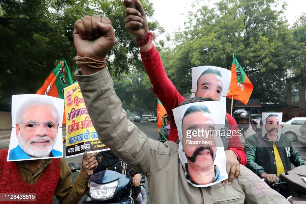 People wear masks in the likeness of Indian Prime Minister Narendra Modi left and Indian Air Force pilot Abhinandan Varthaman during a rally in New...