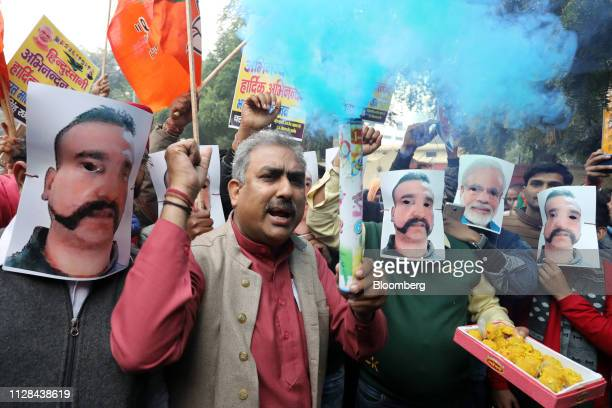 People wear masks in the likeness of Indian Prime Minister Narendra Modi second right and Indian Air Force pilot Abhinandan Varthaman during a rally...