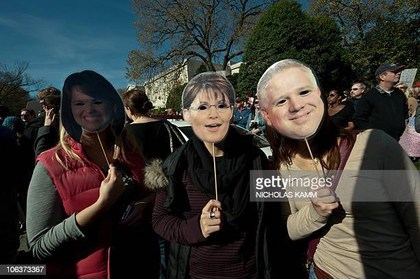 People wear masks of Delaware senatorial candidate Christine O'Donnell former Alaska governor Sarah Palin and conservative radio and television...