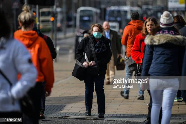 People wear masks on Prince Street on March 17 2020 in Edinburgh ScotlandScottish people have been urged to avoid all nonessential travel and social...