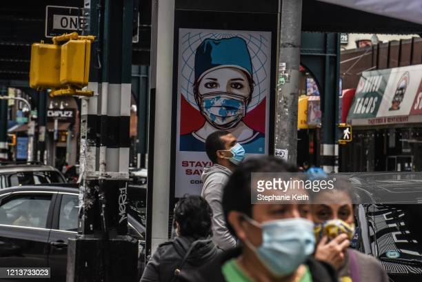 People wear masks on the street on May 18, 2020 in the Elmhurst neighborhood in the Queens borough in New York City. New York City started its ninth...