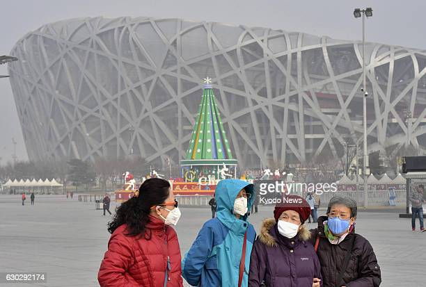 People wear masks to protect themselves against air pollution as they walk near the National Stadium known as the Bird's Nest in Beijing the main...