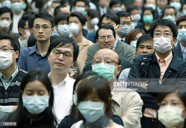 People wear masks to protect themselves against the Severe Acute Respiratory Syndrome virus April 16, 2003 in Hong Kong. The mystery virus has killed...