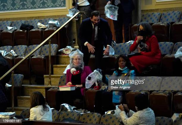 People wear plastic bags s protesters attempt to enter the House Chamber during a joint session of Congress on January 06, 2021 in Washington, DC....