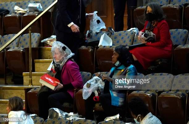 People wear plastic respirators as they are evacuated from the House Chamber as protesters attempt to enter the chamber during a joint session of...