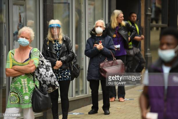 People wear PPE facemasks and visors as they queue to enter a bank in the city centre of Leeds on July 23 as England prepares to make the wearing of...