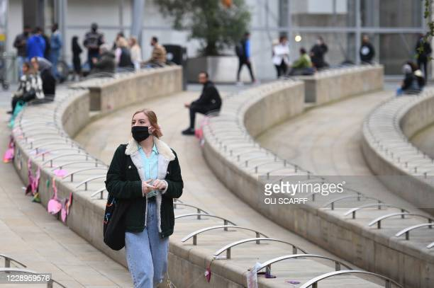 People wear PPE masks and face coverings as they walk through the city centre in Manchester, north west England on October 8, 2020. - Pubs and...