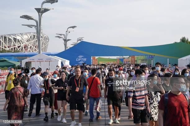 People wear protective face masks as they visit the 2020 China International Fair for Trade in Services at Beijing Olympic Park on September 5, 2020...