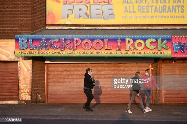 People wear protective face masks as they walk in the evening sunshine along a street in Blackpool northwest England on March 26 2020 The coronavirus...