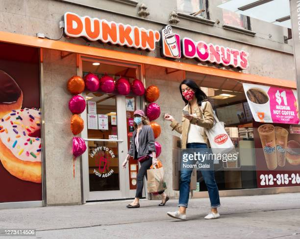 People wear protective face masks outside Dunkin' Donuts in Hell's Kitchen as the city continues Phase 4 of reopening following restrictions imposed...