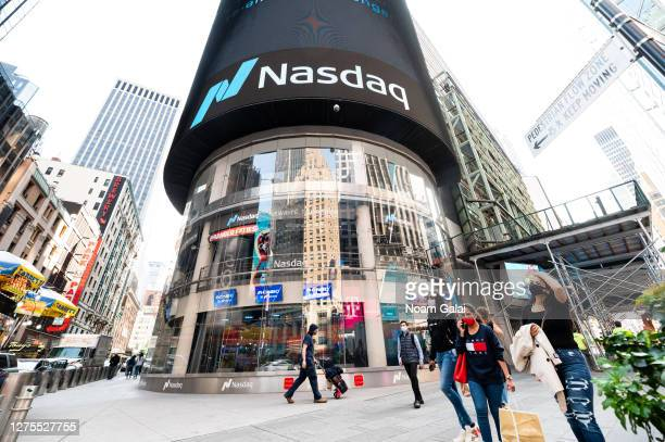 People wear protective face masks outside Nasdaq in Times Square as the city continues Phase 4 of re-opening following restrictions imposed to slow...