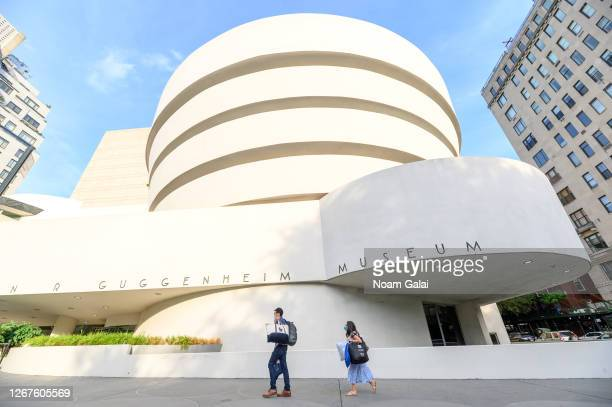 People wear protective face masks outside Solomon R. Guggenheim Museum as the city continues Phase 4 of re-opening following restrictions imposed to...