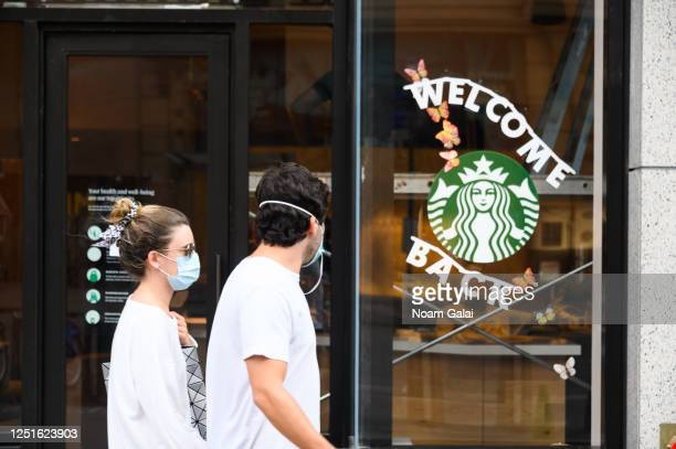 People wear protective face masks outside Starbucks in midtown as the city moves into Phase 2 of re-opening following restrictions imposed to curb...