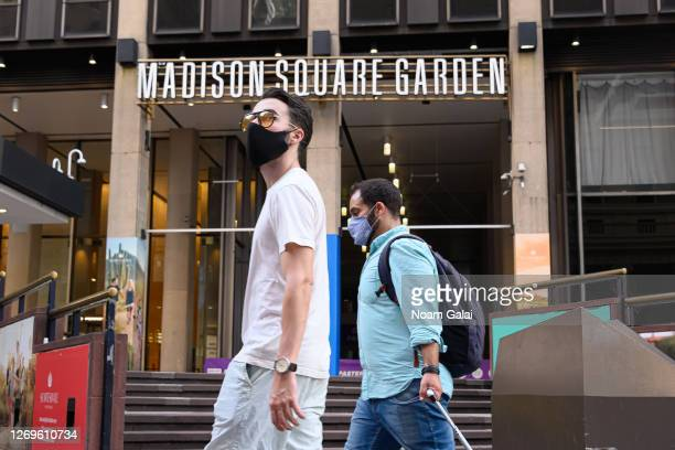 People wear protective face masks outside the Madison Square Garden as the city continues Phase 4 of reopening following restrictions imposed to slow...