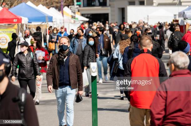 People wear protective face masks while shopping at the Union Square Greenmarket amid the coronavirus pandemic on March 10, 2021 in New York City. It...