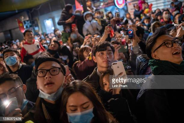 People wear protective face masks while watching fireworks during a public New Year's Eve countdown party in the city center on January 01, 2021 in...