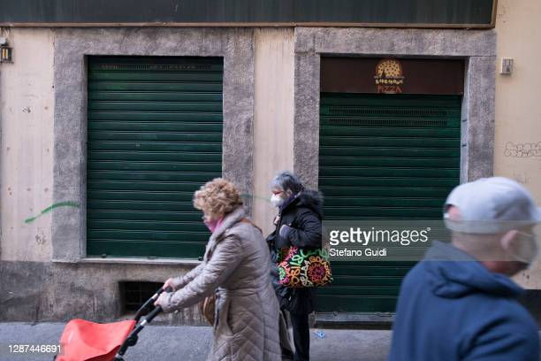 People wear protective mask walks near closed shop in Via Barbaroux on November 24 2020 in Turin Italy Via Barbaroux is an old area in Turin which...
