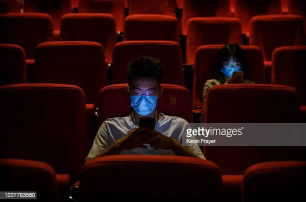 People wear protective masks as they check their smartphones before the start of the film in 3D at a theatre on the first day they were permitted to...