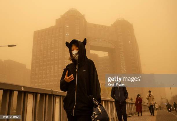 People wear protective masks as they commute during a sandstorm on March 15, 2021 in Beijing, China. The Chinese capital and the northern parts of...