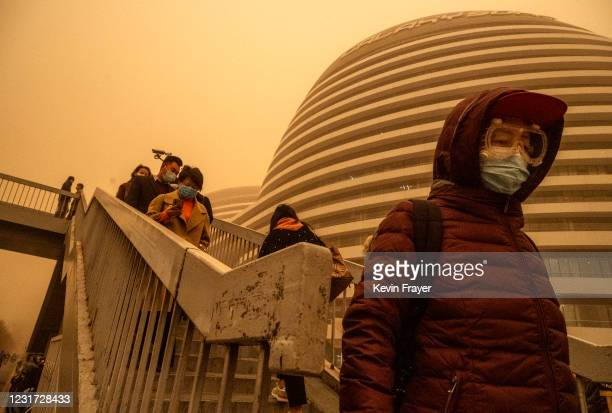 People wear protective masks as they commute during a sandstorm on March 15, 2021 in Beijing, China. China's capital and the northern part of the...