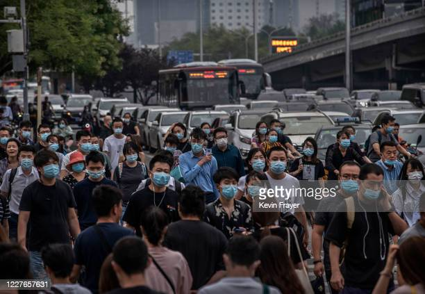 People wear protective masks as they cross an intersection during rush hour on July 17 2020 in Beijing China Chinas economy returned to growth in the...