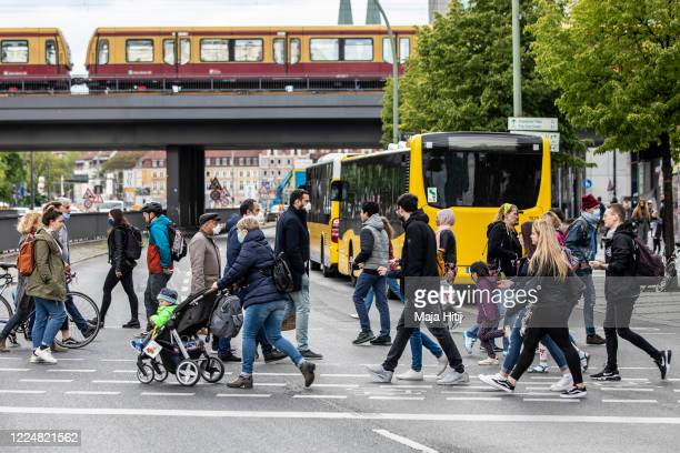 People wear protective masks as they cross the street near Alexanderplatz on May 14 in Berlin Germany As authorities continue to ease lockdown...