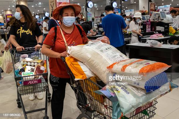 People wear protective masks as they line up to pay in a supermarket on August 2, 2021 in Wuhan, Hubei Province, China. According to media reports,...