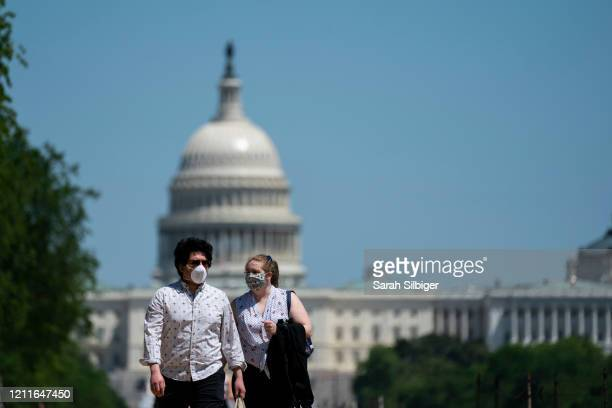 People wear protective masks as they spend time on the National Mall on May 2 2020 in Washington DC Earlier in the day large groups of people...