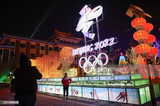 People wear protective masks as they walk front the logos of the 2022 Beijing Winter Olympics at Yanqing Ice Festival on February 26, 2021 in...