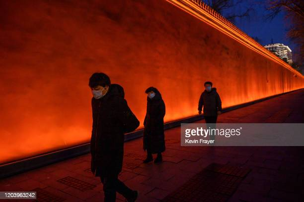 People wear protective masks as they walk in an area usually busy with tourists near Tiananmen Square on February 28 2020 in Beijing China The number...