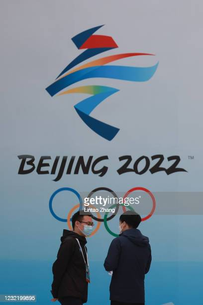 People wear protective masks as they walk in front the logos of the 2022 Beijing Winter Olympics at National Aquatics Centre on April 9, 2021 in...