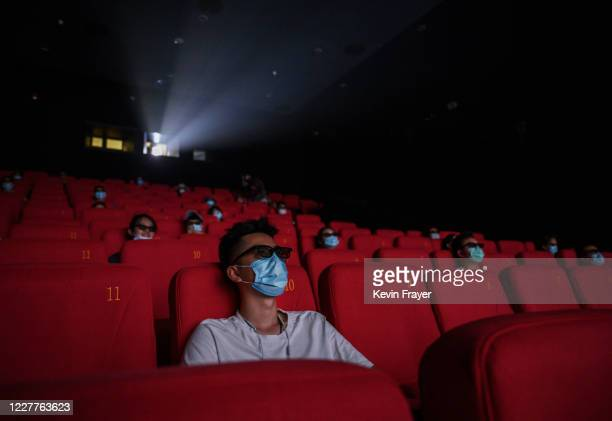 People wear protective masks as they watch a movie in 3D at a theatre on the first day they were permitted to open on July 24, 2020 in Beijing,...