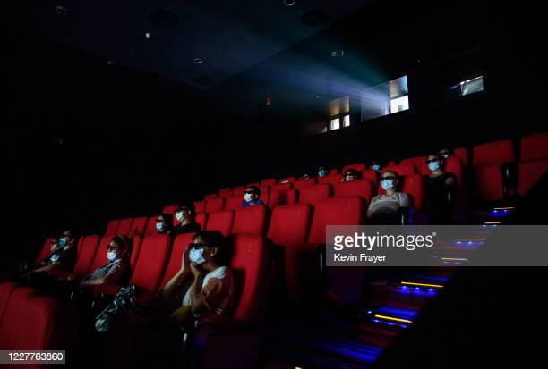 People wear protective masks as they watch a movie in 3D at a theatre on the first day they were permitted to open on July 24 2020 in Beijing China...