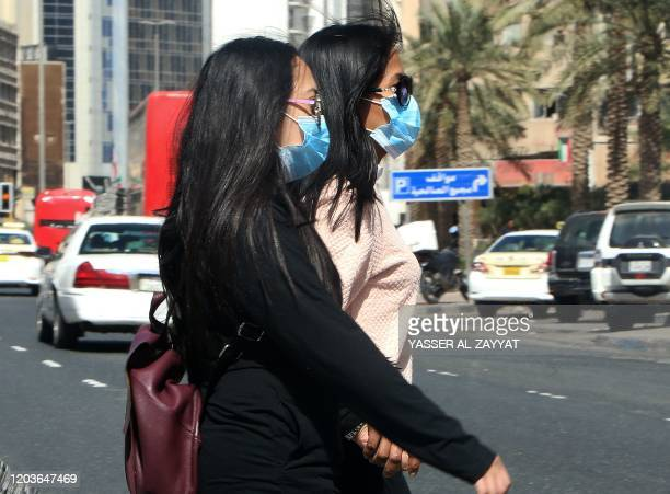 People wear protective masks in Kuwait City on February 27 2020 amidst a world epidemic of cononavirus COVID19 The new coronavirus hit four more...