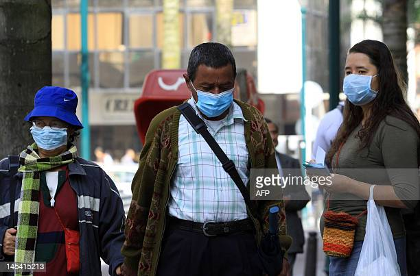 People wear protective masks in Manizales on May 29 due to the ashes spewed from the The Nevado del Ruiz volcano, located on the border of the...