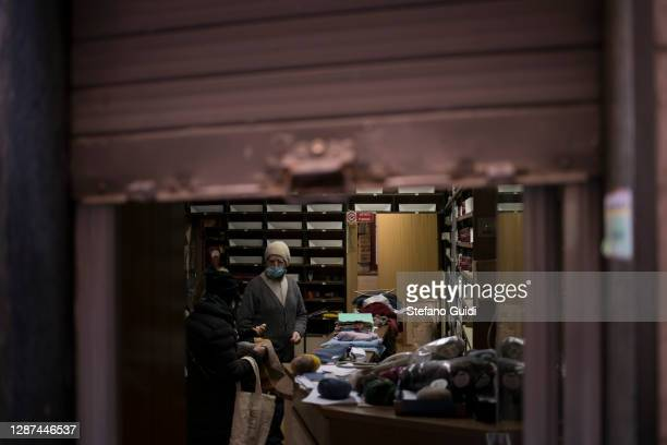 People wear protective masks inside a tailor shop with the shutters down in Via Barbaroux on November 24 2020 in Turin Italy Via Barbaroux is an old...
