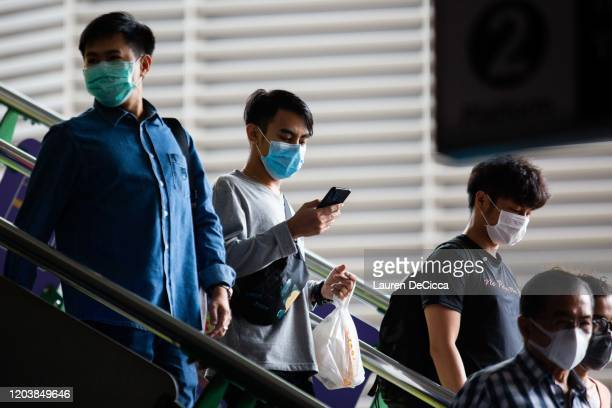 People wear surgical face masks on the Asoke BTS platform on February 28 2020 in Bangkok Thailand Thai citizens and tourists have taken measures such...