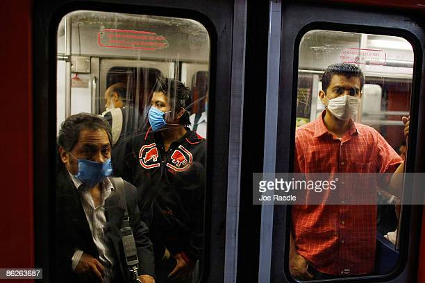 People wear surgical masks as they ride the subway on April 28 2009 in Mexico City Mexico Reports indicate that most people confirmed with the new...